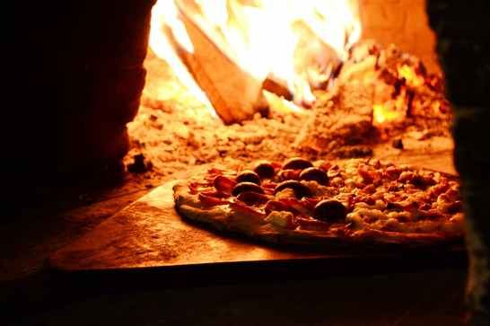 close up photo of pizza near bonfire